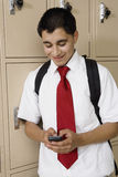 High School Boy Text Messaging By School Lockers. Happy male student using cell phone to text message by school lockers Royalty Free Stock Image