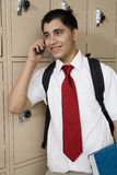 High School Boy Using Cell Phone By School Lockers royalty free stock photography