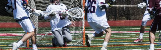 Lacrosse goalie blocks ball. High school boys lacrosse golie blocks a shot during a game stock images