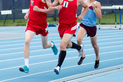 High school boys racing. Three high school boys compete in a track race, running around the final turn before the finish line stock images
