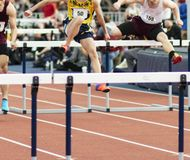 High school boys tied running hurdle race indoors. Three high school boys are alomost tied while running an indoor hurdle race at a track and field competiton stock images