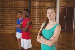 A High School caçoa a posição com os braços cruzados no campo de básquete Imagens de Stock Royalty Free