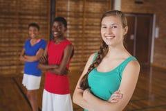 A High School caçoa a posição com os braços cruzados no campo de básquete Imagens de Stock