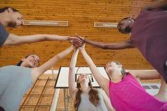 A High School caçoa unir suas mãos no campo de básquete Foto de Stock Royalty Free