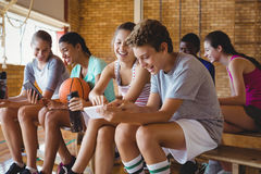 A High School caçoa usando o telefone celular ao relaxar no campo de básquete Imagem de Stock Royalty Free