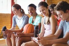 A High School caçoa usando o telefone celular ao relaxar no campo de básquete Imagem de Stock