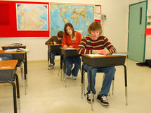 High School Classroom. Three students in classroom, girl might be cheating over shoulder Royalty Free Stock Photography