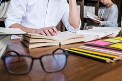 High school or college student group sitting at desk in library. Studying and reading, doing homework and lesson practice preparing exam to entrance, education stock image