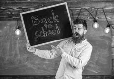 High school concept. Teacher in eyeglasses holds blackboard with title back to school. Man with beard and mustache on. Surprised face welcomes students royalty free stock image