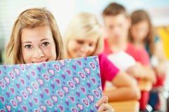 High School: Cute Girl Peeking Over Book Royalty Free Stock Photos