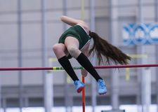 High school female pole vaulter clearing the bar stock photography