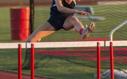 High school female racing in the hurdles. A high school girl is running the hurdles during a track and field competition outdoors on a sunny afternoon stock images