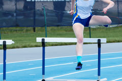 High school female running the long hurdles Royalty Free Stock Images