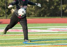 Soccer goalie kicking the ball. A high school female soccer goalie is winding up to kick the ball down the field during a game Royalty Free Stock Image