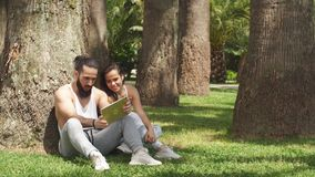 Man and woman relaxing with digital tablet in park after sports training stock video