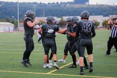 High school football celebration. High school football players on field celebrating a successful play royalty free stock photos