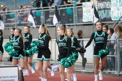 High school football cheerleaders. Cheerleaders performing at high school football game stock photography