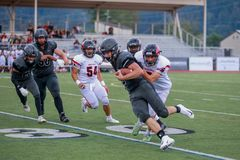 High school football game. High school football players in action during a game, as the player from one team carrying the ball is being pursued by members of the royalty free stock images