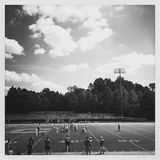 High school football game. Players, coaches and referees on field during a high school football field in black and white stock photos