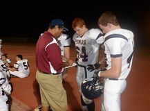 High School Football. Coaches giving instruction for his players to follow when they get back into the game during at a local High School in the in the East stock image