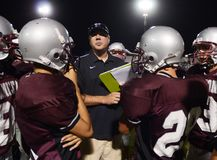 High School Football. Coaches giving instruction for his players to follow when they get back into the game during at a local High School in the in the East stock photography
