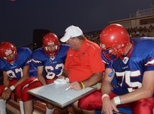 High School Football. Coaches giving instruction for his players to follow when they get back into the game during at a local High School in the in the East royalty free stock photography