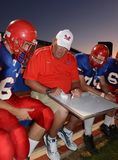 High School Football. Coaches giving instruction for his players to follow when they get back into the game during at a local High School in the in the East royalty free stock photo