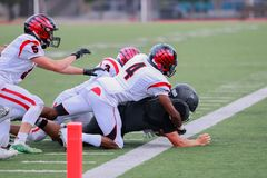 High school football match. High school football players fighting for the ball on the pitch royalty free stock image