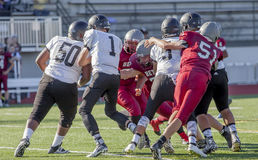 High school football match. High school football teams fighting for the ball on the pitch royalty free stock image
