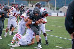 High school football play. Ers during a game play of a player running with the football while his teammates attempt to stop the other team from tackling him stock photos