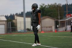 High school football player. In an all black uniform standing on a yard line on field stock images