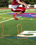 High school football player bounding over hurdles Royalty Free Stock Photo