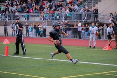 High school football player touchdown. High school football player making a touchdown in the end zone with the official and spectators visible beyond royalty free stock photos