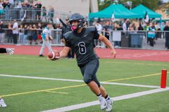 High School Football Player Passing The Ball. A high school football player passes the ball to his teammate royalty free stock photo