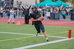 High school football player running with ball. A high school football player running on the pitch while carrying the ball stock photos