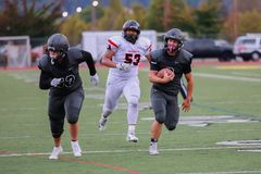 A High School Football Player Running With The Ball. A high school football player runs with the ball while his teammate guards him from being tackled stock photo