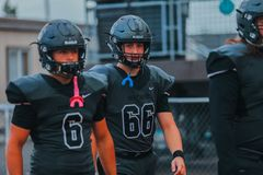 High school football players. A pair of high school football players entering the field royalty free stock image