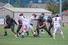 High School Football Rush. High school football players rush each other during a game royalty free stock photography