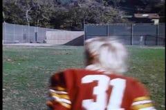 High school football team and coach running across field stock video