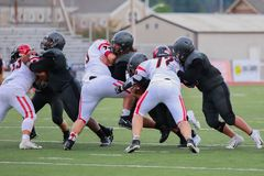 High school football players fighting on pitch. High school football team members fighting on the pitch stock photo