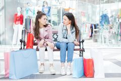 High school friends hanging out in shopping mall. Serious pensive female teenage friends in casual clothing sitting on bench and discussing purchases in modern Stock Photos