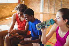 High school girl drinking water while boys using mobile phone Royalty Free Stock Photos
