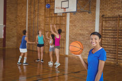 High school girl holding a basketball while team playing in background. Portrait of high school girl holding a basketball while team playing in background Stock Photography