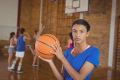 High school girl holding a basketball while team playing in background. Portrait of high school girl holding a basketball while team playing in background Stock Image