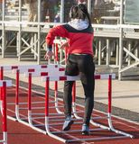 Female hurdle runner wearing headphones stock images