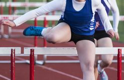 High school girl racing the hurdles. A front view of a high school girl racing the high hurdles in competition outdoors royalty free stock images