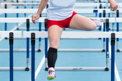 High school girl racing in the hurdles. High school girl racing the hurdles at a track and field competition stock photo