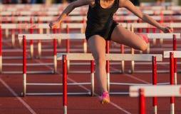 High school girl racing the 100 meter hurdles stock image