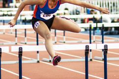 High school female running in hurdle race indoors. A high school girl racing in the 55 meter hurdles at an indoor track and field race stock photos