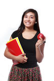 High School Girl Ready for Back to School. Attractive latina high school girl holding some notebooks and an apple ready to go back to school isolated on a white royalty free stock photography